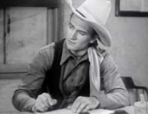 John Wayne looks up from doing some paperwork in Texas Terror