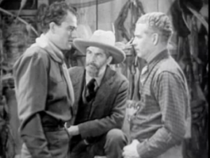 Ed (Gabby Hayes, centre) watches John (John Wayne, left) talk to an unidentified man in Texas Terror.