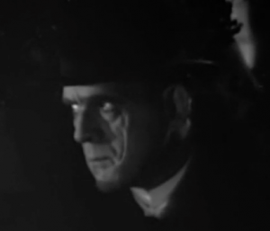Valdar (Boris Karloff) listens in the shadows in British Intelligence