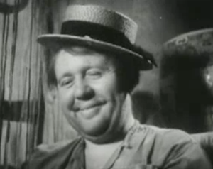 Charles Laughton, smiling with a straw hat tilted on his head, in The Beachcomber.