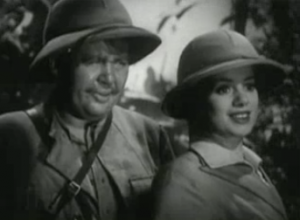 Both wearing pith helmets, Ted (Charles Laughton) peers at a smiling Martha (Elsa Lanchester) in The Beachcomber.