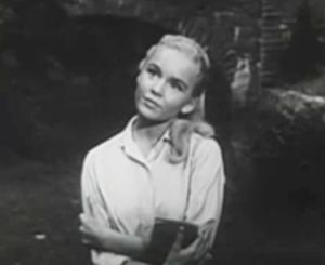 Dori (Tuesday Weld), long blonde hair over one shoulder, gazes upward in a park in Rock Rock Rock!