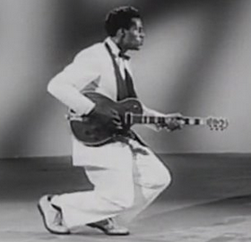 Chuck Berry plays his guitar while walking with his knees deeply bent in Rock Rock Rock!