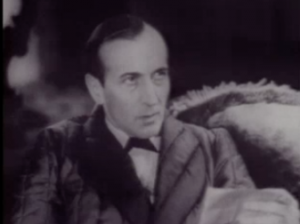 Sitting on a sofa, Sherlock Holmes (Arthur Wontner) looks up from reading a document in Murder at the Baskervilles.