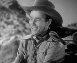 Wearing a cowboy hat and a bandana around his neck, Jeff (Roy Rogers) smiles as he drives a stagecoach in Nevada City.