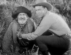 Jeff (Roy Rogers, right) helps Gabby (Gabby Hayes, left with beard) after he's fallen, in Nevada City.