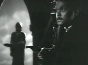 In the clock tower, Rankin (Orson Welles) aims a pistol as a figure on the clock holds a sword in The Stranger.