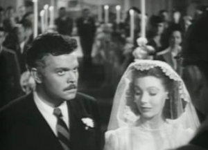Married in a church lined with candles, Rankin (Orson Welles, with curly dark hair and moustache) looks ahead as Mary (Loretta Young, in wedding gown), looks down under her veil in The Stranger.