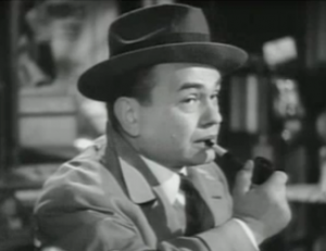 Wilson (Edward G. Robinson), in trenchcoat and hat, smokes his pipe which has been mended with tape, in The Stranger.