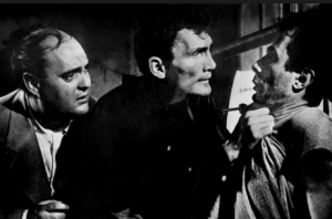 Blackie (Jack Palance) grabs the Poldi (Guy Thomajan) by his shirt as Fitch (Zero Mostel) looks on fearfully.