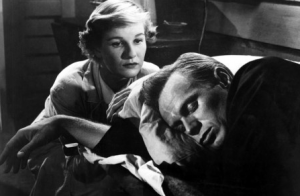 With short blonde hair, Nancy (Barbara Bel Geddes) gazes at her dozing blond husband Clint (Richard Widmark).