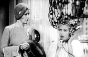With her hair in curlers hanging from black electrical cords, Schatzi (Joan Blondell) has a surprised expression with a phone to her ear as Jean (Ina Claire) looks on.
