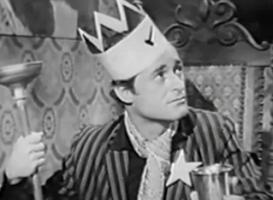 Looking up and to the side, Walter (Dick Miller) wears a striped jacket with a paper star on it and a paper crown as he holds a plunger as a sceptre in one hand and a goblet in the other.