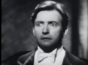Maximus (Claude Rains), in white tie, stares intently and a little startled while lit by stage light.