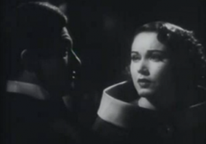 With dark wavy hair and a wide collar surrounding her neck, Rene (Fay Wray) looks forlorn to Max (Claude Rains), who's shown in profile in shadow.