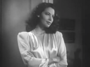 With wavy dark hair and wearing a white silk dressing gown, Mary (Ava Gardner) leans in a doorway with her arms crossed and a half-smile.