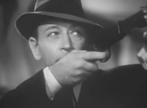 Wearing a suit and fedora, Kenny (George Raft) aims a rifle for carnival games upward.