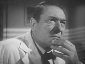 Wearing a white jacket and shirt with black bowtie, Gitlo (Victor McLaglen) listens thoughtfully with fingers on his chin.