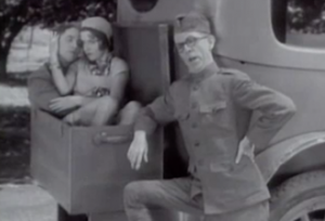Wearing a military uniform, Gilbert (Robert Woolsey) leans on the back of a car talking while Tommy (Bert Wheeler) and Annette (Dorothy Lee) cuddle in the open trunk.
