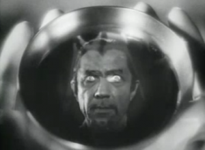 An image of Legendre (Bela Lugosi), with van dyke beard, widows peak hair and glowing eyes, appears in a wine goblet.