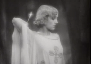 With short, wavy blonde hair, Madeleine (Madge Bellamy) holds a gleaming knife behind her head as she stares down blankly.