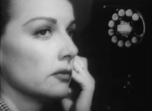 Eleanor (Ann Sheridan), listens on a telephone as she watches ahead warily, in Woman On the Run.