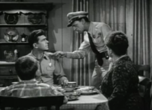 Barney Fife (Don Knotts) stands pointing at Andy (Andy Griffith) as he sits at the dinner table with Opie (Ronny Howard) and Aunt Bea (Francis Xavier)
