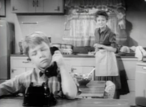 Opie (Ronny Howard) listens on a telephone as Thelma Lou (Betty Lynn) watches from her kitchen sink, smiling.