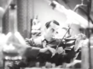 Framed by laboratory equipment, Sherlock Holmes (Arthur Wontner) sits playing his violin.