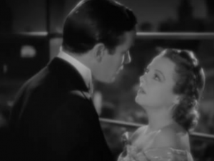 In evening wear, Duncan (Richard Carlson) holds George-Anne (Janet Gaynor) by the arms as she stares up at him with her mouth open.