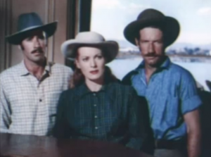 All wearing flat-brimmed Bush hats, Connor (Peter Lawford), Dell (Maureen O'Hara) and Gamble (Richard Boone) watch Dell's father. Both Connor and Gamble have moustaches.