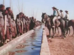 The white ranchers face a very long line of Aboriginal people with an equally-long water trough between them.