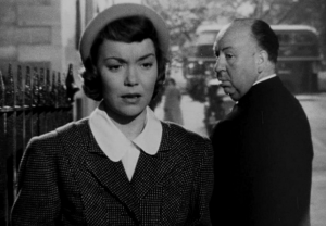 On a sidewalk, Eve (Jane Wyman) considers something while a balding, stocky man (Alfred Hitchcock) turns back to stare at her.