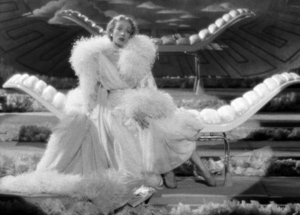Wearing a voluminous white dressing gown and feather boa, Charlotte (Marlene Dietrich) sits on a lounge as she performs onstage.