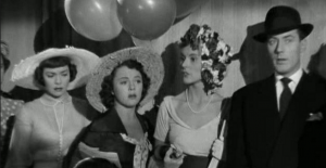 In a fair tent decorated with balloons, Eve (Jane Wyman), Chubby (Patricia Hitchcock) and Smith (Michael Wilding) look nervous as Valerie (Josephine Douglas) talks.