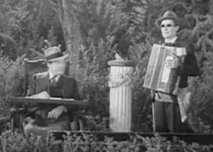In a park, Flint (Lionel Atwill) sits in his wheelchair with a tray of pamphlets on the arms. On the other side of a sundial, Marchant (Henry B. Walthal) stands with dark glasses and an accordion.