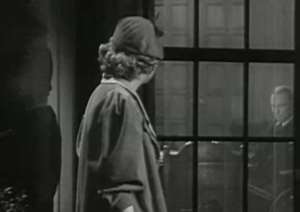 Outside at night, Joyce (Betty Furness) peers in through a window at her long-lost father Flint (Lionel Atwill) at his desk.