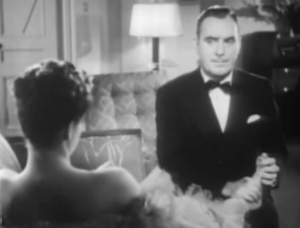 In a tuxedo, John Webb (Pat O'Brien) frowns as he holds Ann's (Ruth Terry) bare foot.