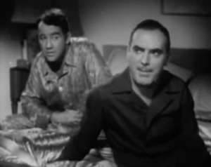 Both wearing pyjamas, John (Pat O'Brien) sits on the front corner of a bed talking as Russ (Broderick Crawford) sits on the other side watching him.