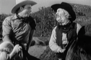 Both on horseback, Brett (Roy Rogers) smiles at Gabby (Gabby Hayes) as he talks.