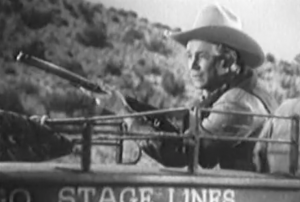 Turned on the driver's seat of a stagecoach, Brett (Roy Rogers) holds his rifle and watches his pursuers behind him.
