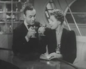 Michel (Charles Boyer) and Terry (Irene Dunne) toast with pink champagne at a bar on their ship.