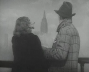 On the deck of the ship, Terry (Irene Dunne) points out the Empire State Building in the distance to Michel (Charles Boyer).