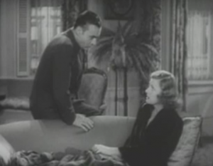 Michel (Charles Boyer) leans on the back of a sofa speaking with Terry (Irene Dunne) who sits on the sofa with her legs covered by a blanket.