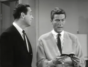 Rob (Dick Van Dyke) stares ahead holding a small bank book open as Jerry (Jerry Paris) speaks to him.