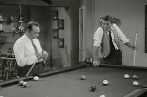 As he leans with fatigue on his pool table, Rob (Dick Van Dyke) notices Blackie (Phil Leeds) taking out a container of powder.