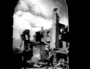 Viewed through an arch, a shirtless man stalks past some of the towering rubble of Everytown.