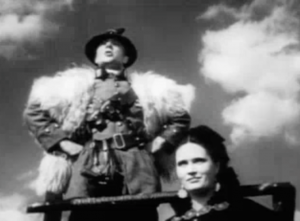 Wearing a helmet and a fur cape and with his fists on his hips, The Boss (Ralph Richardson) addresses his troops on a platform with Roxana (Margaretta Scott) smirking below him.