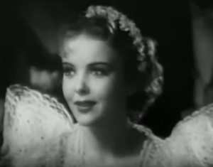 Monique (Ida Lupino) smiles warmly, wearing a gown with poufed shoulders and flowers in her short blonde curly hair.