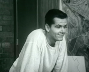 With short black hair and wearing a baggy white sweatshirt, Johnny (Jack Nicholson) leans forward on a desk and grins.
